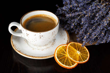 The cup of morning coffee on a dark background. Orange and lavender flowers nearby.