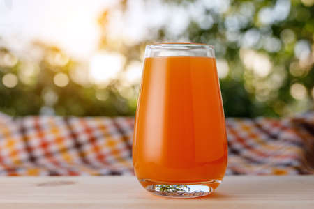 The glass of juice in a garden. The wooden table. Stock fotó