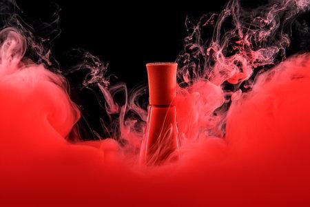 Red nail polish envelops jar on black background