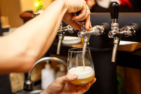 Pouring beer from tap in a bar