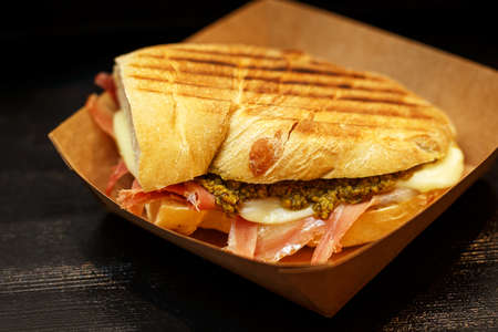 Sandwich with bacon and spinach in a cardboard box