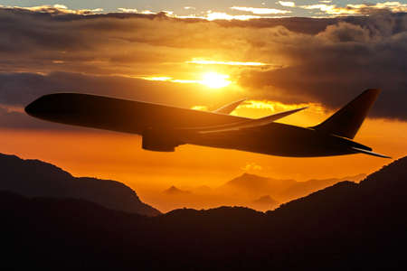Black silhouette of an airplane over the mountains on sunset Reklamní fotografie