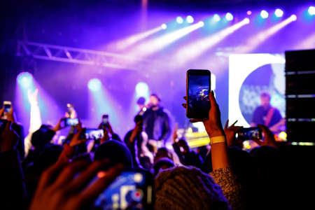 Recording a concert with mobile phone, silhouette of hands with smartphone
