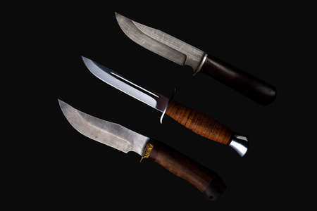 Set of knifes made of Damascus steel with a wooden handle on a isolated dark background.
