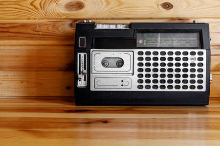 Old cassette tape recorder on wooden background