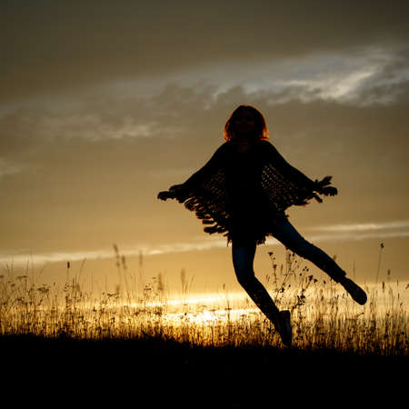 Happy Woman Jumping in field on Sunset Stock Photo