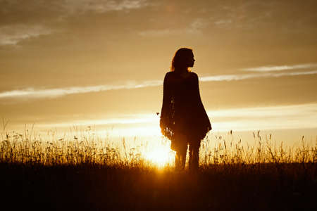 silhouette of happy young woman on sunset, outdoor girl in a plaid poncho Stock Photo