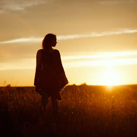 silhouette of happy young woman on sunset, outdoor girl in a plaid poncho in a field with spikelets