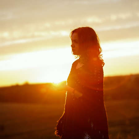 Happy young woman on sunset, outdoor girl in a plaid poncho in a field with spikelets