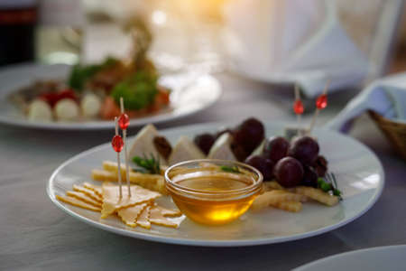 Honey on a plate with cheese and grape. Stock Photo