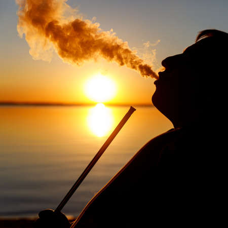 Black silhouette of the man who is smoking hookah at sunset