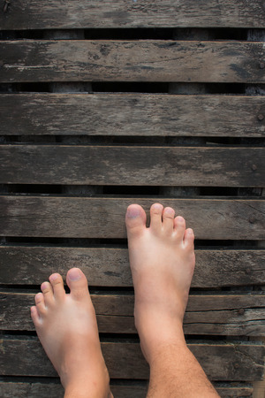 Cropped image of male bare feet on a wooden floor Stock Photo