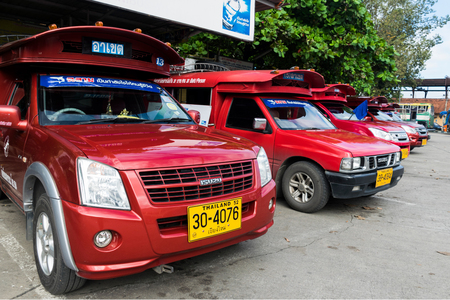 CHIANG MAI, THAILAND - OCTOBER 7: Iconic traditional red truck taxis parked and waiting for the passenger at Arcade bus station in Chiang Mai, Thailand
