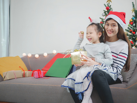 Asian young mother presents gift and enjoying their time together. Focus on the little girl.