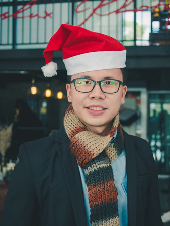 Portrait of young Asian man with Christmas Santa hat standing in coffee shop.