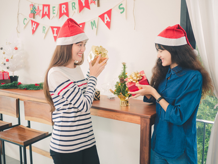 Two asia women holding gift box in christmas party, Have Christmas Tree Ornaments.