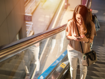 Young asian woman standing escalator and smiling, Using smartphone searching for social media in the city.