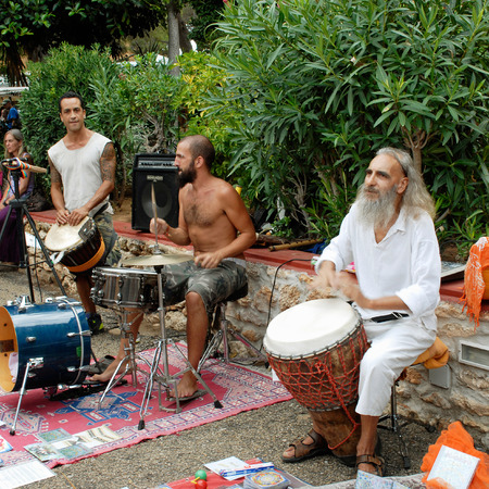 percussionist: Es Cana, Ibiza, Spain - August 28th, 2013: Local musicians playing drums at the hippy market in the resort of Es Cana Ibiza. The market is held every Wednesday during the summer months, selling local arts and crafts, clothing etc. In 2013 the market celeb Editorial