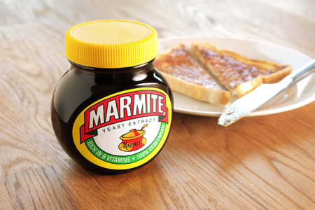 distinctive flavor: Leeds, United Kingdom - April 22nd, 2015: Jar of Marmite, unopened on wooden table top. Slice of toast on a white plate in background. Marmite is a food paste, made from yeast extract and has a distinctive salty flavor.
