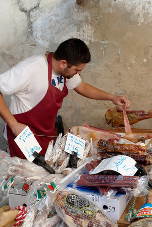 Pollenca, Mallorca, Spain - September 14th 2008: A local butcher slicing meat on a stall at the local market in the town of Pollenca, Mallorca, Spain.