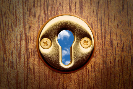 close out: Close up of a keyhole looking out to the sky beyond Stock Photo