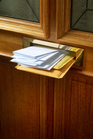 letterbox: A brass letterbox in an external door stuffed with mail Stock Photo