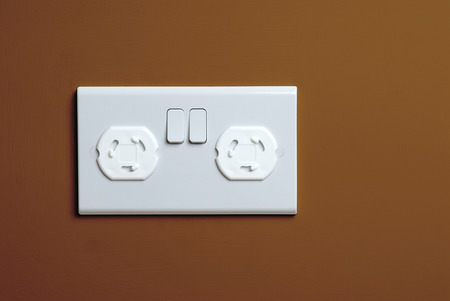 blanking: Closeup of a childproof electrical plug socket. A normal UK double plug socket the plastic plates are inserted into the socket to prevent a child from tampering with it and are removable.