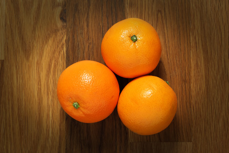table surface: Three oranges shot from above on a wooden table surface