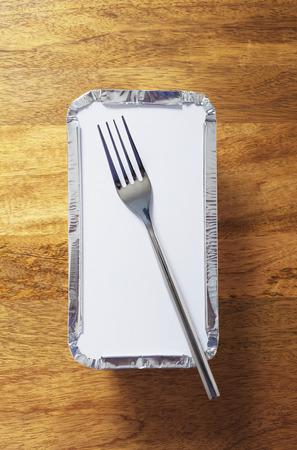 chinesisch essen: Silberfolie Service Tablett mit einer Gabel auf Spitze gesetzt. Erschossen von oben auf Holztisch
