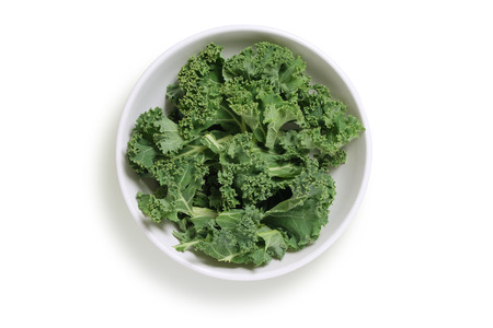 white background: Chopped kale in a white bowl, shot from above isolatd on white with clipping path