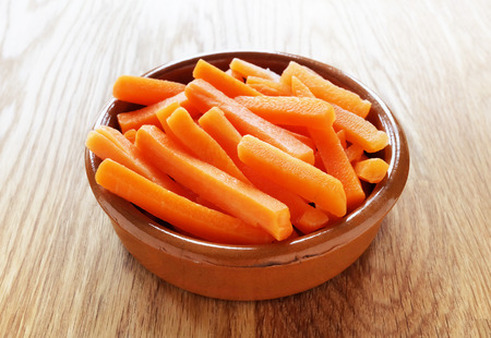 carrots: Raw carrot sticks in brown rustic bowl on wooden table