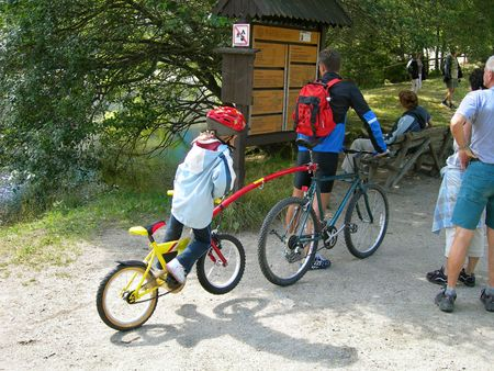 striving: Father and son biking in the mountain on a tandem bike. People relaxing. Stock Photo