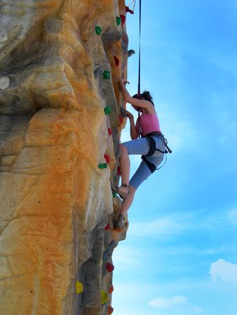 rappelling: Active alpinist girl climbing artificial rock - sport, recreation