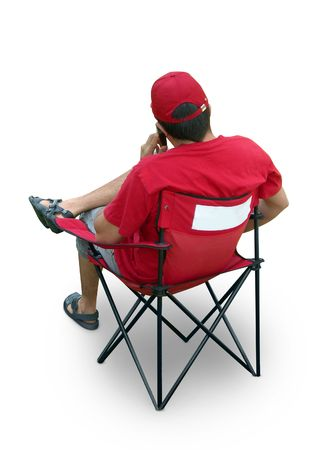 Staff member in red t-shirt and cap sitting in folding chair, place for your logo. Isolated Stock Photo