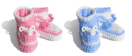 Its a girl, boy. Newborn baby symbols - tiny shoes, socks, bootees. Isolated, shadow Stock Photo