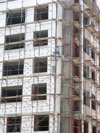 staging: Newly built block of flats with scaffolding, thermo-insulation, workers Stock Photo