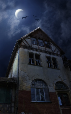 Old ruined sinister house in Halloween night. Bats flying in the sky with Moon and clouds photo
