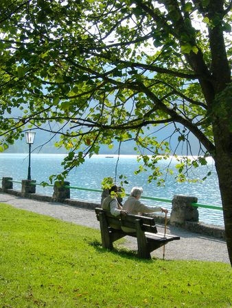Elderly couple on a bench beside a mountain lake - Schliersee