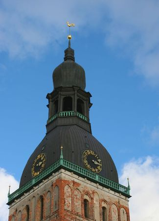 This picture shows tower of the Dome Cathedral (Riga, Latvia). The cornerstone for the Dome Cathedral was laid on 1211. The architecture of the church includes elements of Early Gothic, Baroque and other styles, but the main building and the attached cloi photo