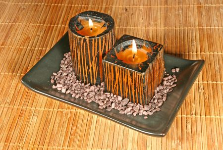 Two candles on a bamboo mat photo