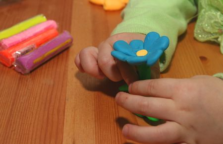 The hands of a three year old, making a flower out of plasticine