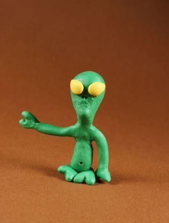 Plasticine figure of alien, on brown photo