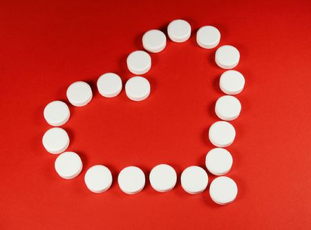 White pills forming a heart shape, on red.