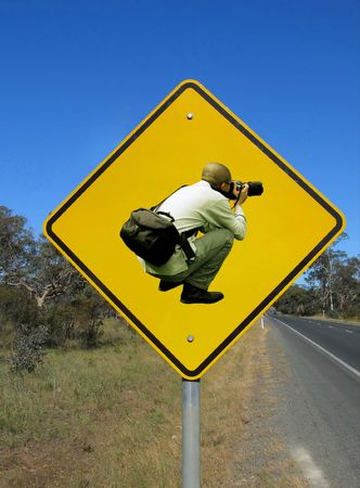 Caution photographers ahead. Funny road sign agains the blue sky.