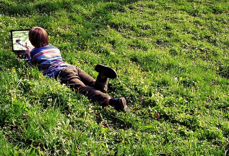 To see itself! Child with notebook lays on a grass. (raw,tiff version of this image is available - contact me) photo