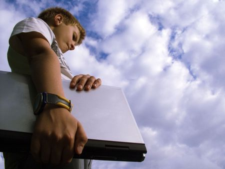 The child with a portable computer in the blue sky. photo