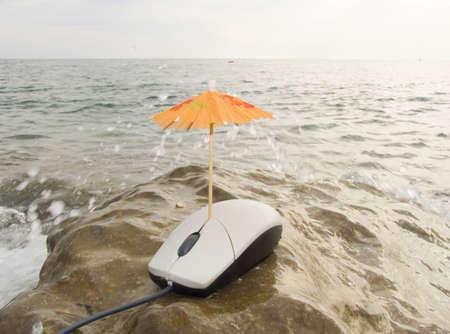 turismo ecologico: El rat�n de la computadora bajo un paraguas en la costa mar�tima bajo las chispas de agua