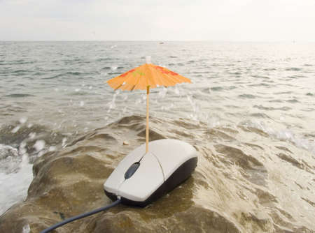 The computer mouse under a umbrella on seacoast under sparks of water