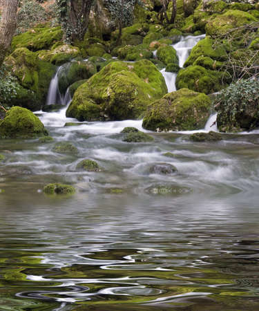 Falls on the mountain river with boulders the overgrown with a moss