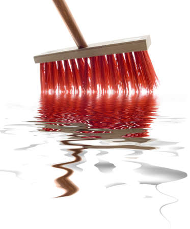 The red brush on the wooden handle cleans water from a floor